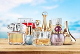 Aromatic Perfume bottles on wooden table on blurred background - 232217177