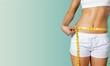 Leinwanddruck Bild - Slim young woman measuring her thin waist