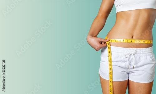 Leinwanddruck Bild Slim young woman measuring her thin waist