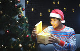 Asian Man With Christmas Costume Opening Shining Gift, Sitting Beside Christmas Tree - 232230715