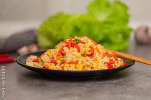 Wall mural Chinese fried rice with vegetables, served on a plate with chopsticks. Selective focus