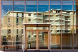 Ein Wohnhaus spiegelt sich in einer Glasfassade - 232235784