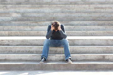 Man sitting on the stairs is saddened and frustrated with life. Concept. Toned photo.