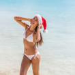 Leinwanddruck Bild - Christmas santa hat bikini body sexy Asian girl happy in sun tan holidays. Spa wellness concept healthy woman for weight loss concept, laser treatment, cellulite, fit body.