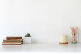 Workspace coffee mug, books, pencil and cactus on white desk. - 232242596