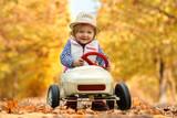 fröhliches Mädchen im Herbst mit Tretauto - 232245150