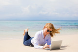 Happy business woman with laptop on the beach