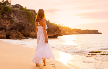 Carefree woman in white dress walking on the beach at sunset © Kaspars Grinvalds