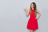 Smiling Beautiful Woman In Red Dress Is Pointing At Gray Copy Space And Looking Away - 232250735