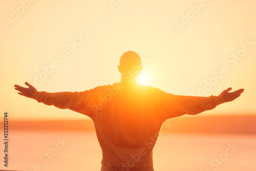 Poster Young athletic man rising hands on sunset sky. Meditation, yoga, freedom and healthy lifestyle concept