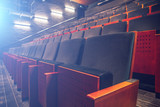 Empty theatre or cinema auditorium hall with rows of seats or chairs with blue spotlights or screen light effect - 232258521