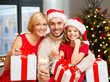 holidays, family and celebration concept - happy mother, father and daughter with gifts and sparklers at home over christmas tree lights background