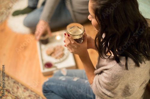 Poster hygge, leisure and people concept - close up of woman drinking coffee with waffles at home