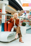 happy attractive woman talking on smartphone and sitting with shopping bags - 232271947