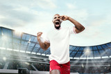 The football player in motion on the field of stadium - 232272338