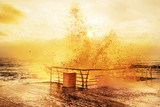 Sunny positive full of energy morning at sea. Waves with splashes crashing on a wooden jetty.