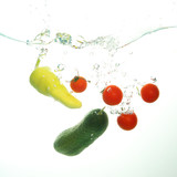 Cherry tomatoes cucumber and green papper under water spash on white © Geza Farkas