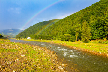 Twin rainbow over the mountain river in Carpathians, Ukraine