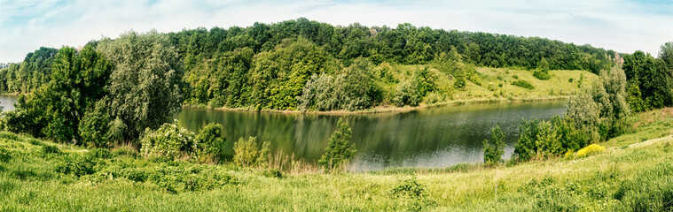Bend of river with green trees and grass on shore © alexlukin
