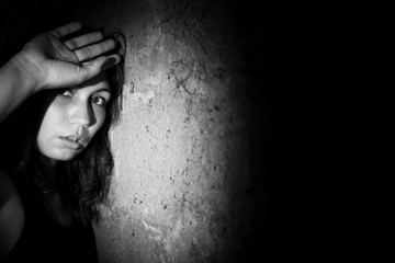 Teenager girl with depression alone in the dark room. Black and white photo