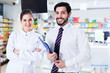 Two pharmacists standing in drugstore
