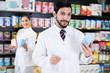 Leinwanddruck Bild - pharmacist standing with medicine on his work place