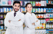 Leinwanddruck Bild - Portrait of two specialistes who are standing near shelves with medicines in pharmacy.