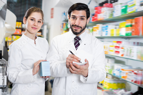 Leinwanddruck Bild Two pharmacists are inventorying medicines with note near shelves in apothecary.