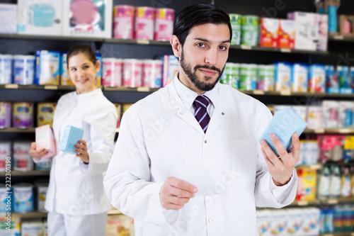 Leinwanddruck Bild pharmacist standing with medicine on his work place