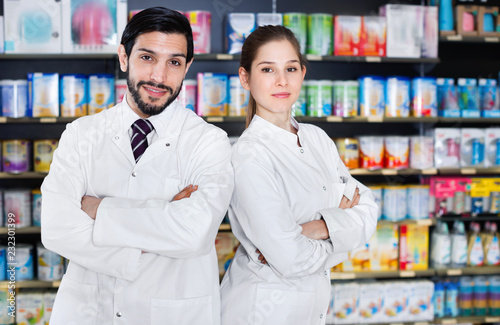 Leinwanddruck Bild Portrait of two specialistes who are standing near shelves with medicines in pharmacy.