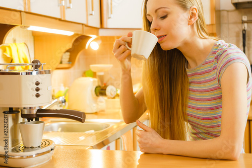 Poster Woman in kitchen making coffee from machine