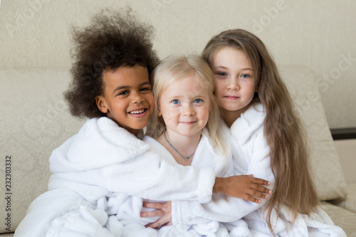Children of different religions hug each other. Girls of different faiths Muslim and Christian women are happy together.