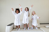 Three little girls dancing on the couch. Girls of different nationalities in white coats dance and laugh after a bath. - 232305128