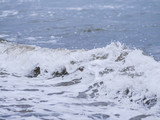 Waves at the seashore. Selective focus with shallow depth of field.
