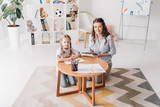 happy psychologist with clipboard sitting near little child while she drawing with color pencils and looking at camera - 232315749