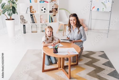 happy psychologist with clipboard sitting near little child while she drawing with color pencils and looking at camera