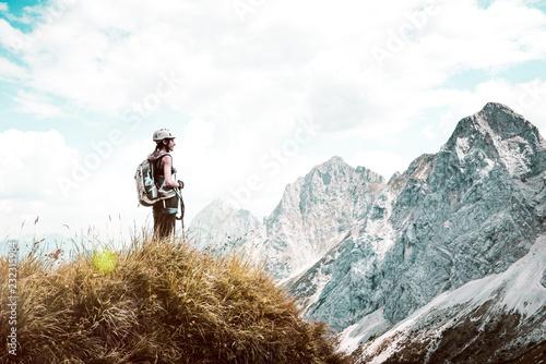 Frau steht aus grasigem Berggipfel