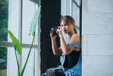 Cute multiracial small girl taking pictures with a professional camera. Photographer. People, photography, technology, leisure and lifestyle - happy young female photographer looking to digital camera - 232317513