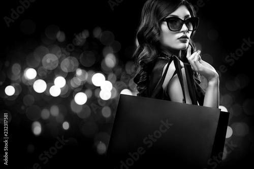 Leinwandbild Motiv Christmas or Black friday sale concept. Shopping woman holding bag on dark background with bokeh in holiday. BW photo.