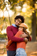 Beautiful couple African American man and Caucasian woman walking in the autumn park