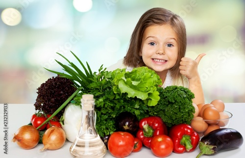 Leinwanddruck Bild Cute little girl with vegetables in kitchen