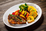 Grilled chicken fillet and vegetables on woowde table - 232332306