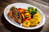 Grilled chicken fillet and vegetables on woowde table - 232332364