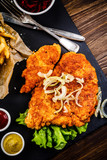 Fried pork chop, French fries and vegetables on wooden background - 232332976
