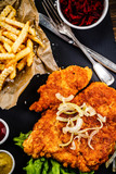 Fried pork chop, French fries and vegetables on wooden background - 232333397