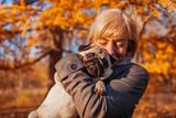 Master walking pug dog in autumn park. Happy woman hugging pet. Friendship between human and animal - 232333948