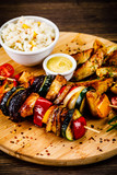 Kebab - grilled meat and vegetables on cutting board on wooden table - 232333973