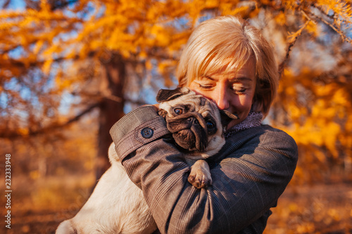 Master walking pug dog in autumn park. Happy woman hugging pet. Friendship between human and animal