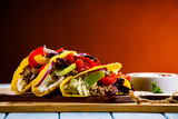 Tacos on cutting board on wooden table - 232334529