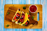 Tacos on cutting board on wooden table - 232334749